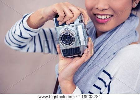 Close up of smiling Asian woman taking photograph with camera