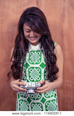 Smiling Asian woman holding camera against wooden wall
