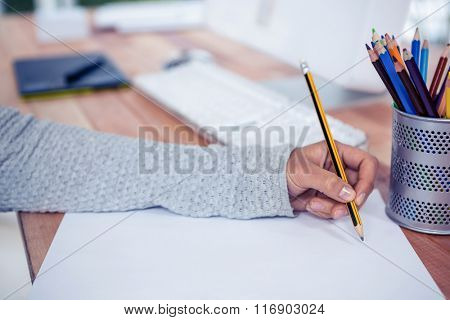 Womans hand drawing with pencil on white sheet in office