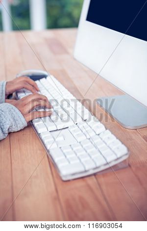 Womans hands typing on computer keyboard in office