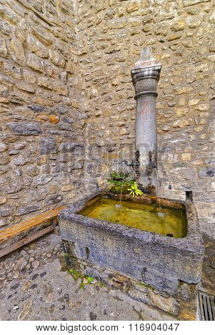 VEYTAUX SWITZERLAND - JANUARY 2 2015: Fountain with drinking water in Courtyard of Chillon Castle. It is an island castle on Lake Geneva (Lac Leman) in the Vaud between Montreux and Villeneuve.
