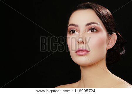 Portrait of young beautiful woman with fresh make-up looking upwards over dark background