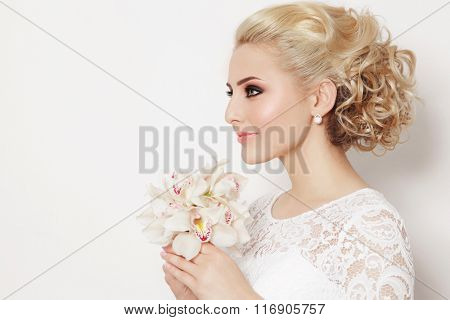 Young beautiful bride with stylish prom hairdo and bouquet of orchids