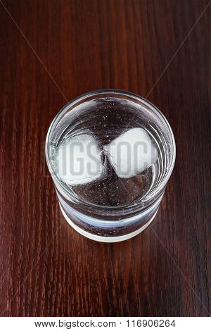 Glass Of Transparent Purified Water With Ice On Wooden Table, Top View