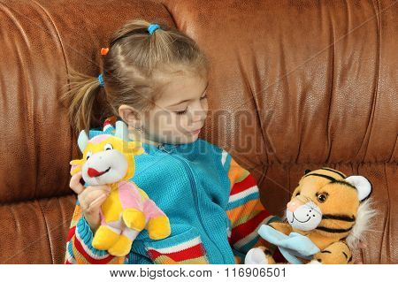 the little girl plays soft toys