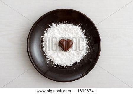 Chocolate Heart-shaped Candy On A Brown Plate With Sugar Powder Against Wooden Background