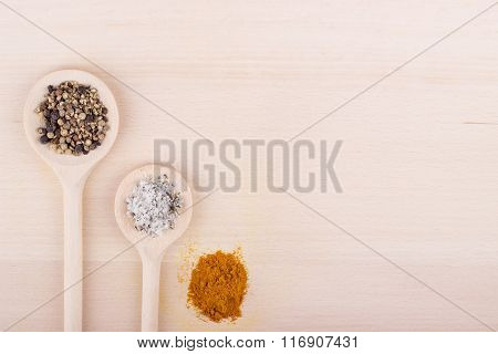 Salt, Pepper And Curry In Spoons On Wooden Background