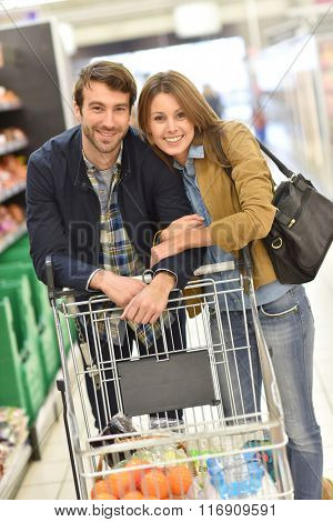 Couple pushing shopping cart in supermarket