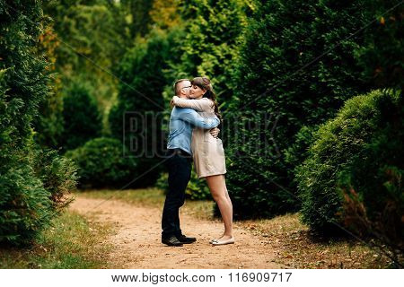 Pregnant Beautiful Woman And Her Handsome Husband Lovely Hugging In Autumn Park.