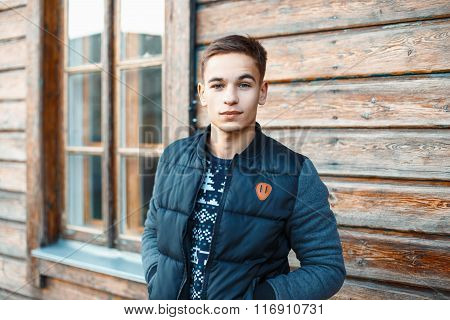 Handsome Young Man In Winter Twist And Knitted Sweater Stands Near The Old Wooden House.