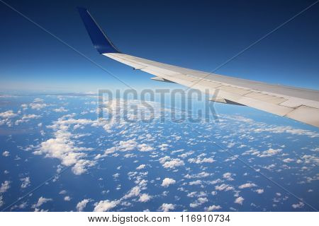 Wing Of Airplane Above White Clouds