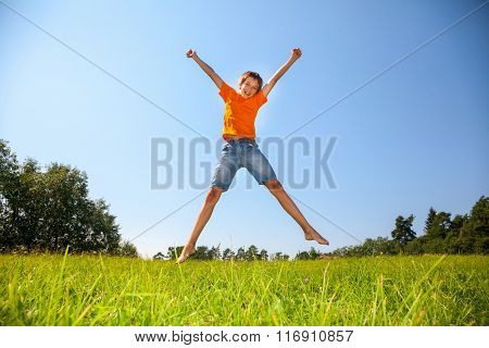 Boy enjoying summertime jumping on the sunny meadow in a summer forest