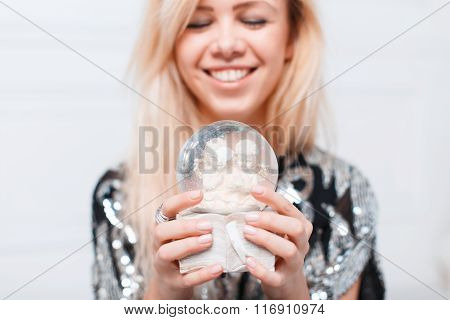 Pretty Woman With A Beautiful Smile Holding A Gift Snow Christmas Ball With Angels.