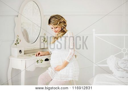 Young Beautiful Pregnant Woman In White Dress Sitting On Chair.