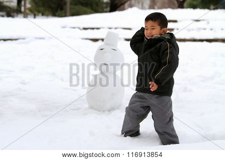 Japanese boy having snowball fight and snowman (4 years old)