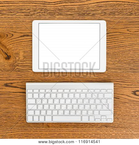 Workplace with white tablet computer and keyboard.