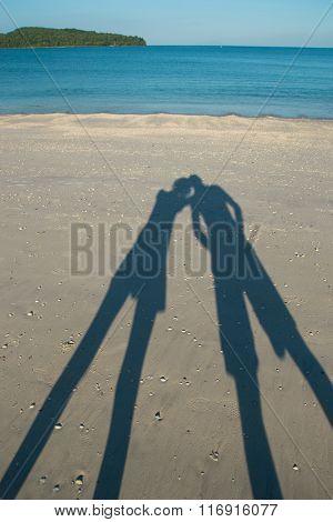 Shadow kissing couple on beach