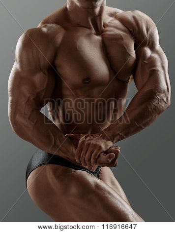 Handsome muscular bodybuilder posing over gray background