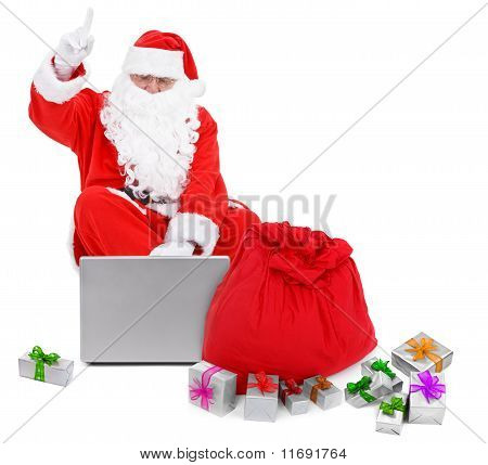 Surprised Santa Claus With Laptop And Presents