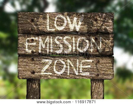 Low emission zone wood sign with foliage at the background