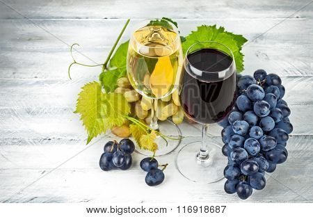 Red white wine in wineglass with grapes green willow wooden board