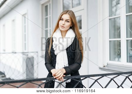 Beautiful Girl With A White Knitted Warm Scarf And A Black Dress Stands Near Home