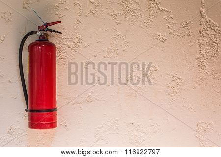 Red fire extinguisher fixed on the wall of the house.