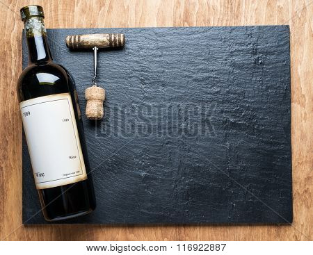 Wine bottle and corkscrew on the graphite board.