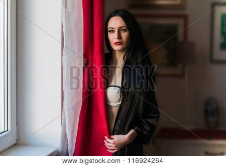 Beautiful young girl in kimono hiding behind the red curtains in the interior near window.