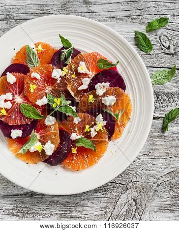 Blood Oranges And Beet Salad With Feta, Mint And Balsamic Dressing On Rustic White Wooden Background