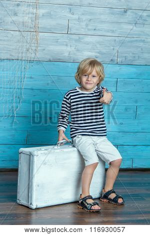 child sitting on a suitcase