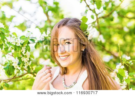 Romantic young woman in the spring garden among apple blossom, soft focus