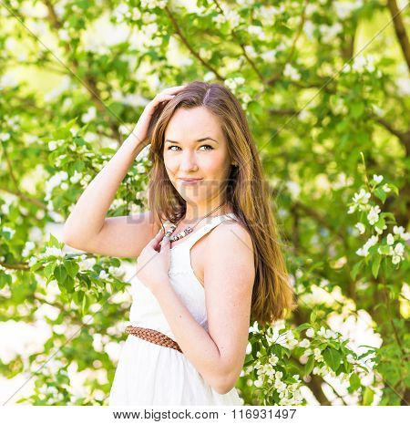 Beautiful young woman in the spring garden among apple blossom, soft focus