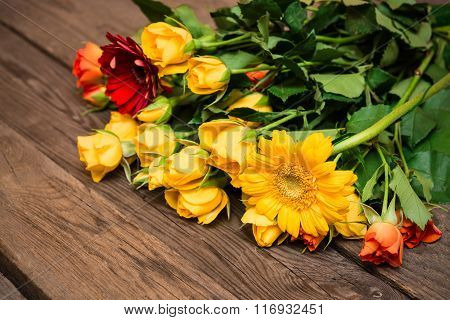 Yellow, Orange Roses And Herberas On A Wooden Background. Women' S Day, Valentines Day, Mothers Day.