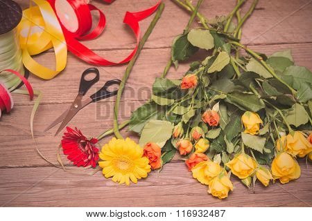 Workplace Of Florist, Making Bouquet. Yellow And Orange Roses On A Wooden Background.