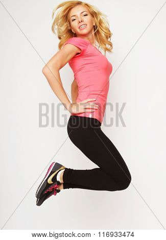 Excited sporty woman jumping.