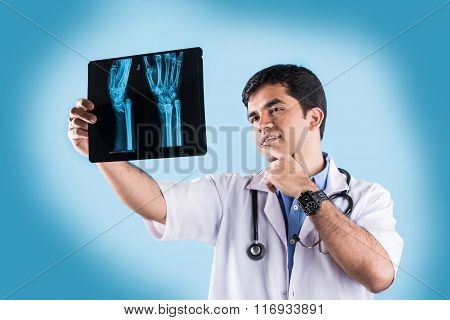 young indian male doctor with x ray, asian male doctor with xray or xray, isolated on blue backgroun