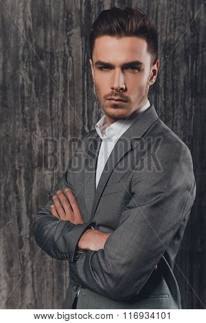 Handome Brutal Man In Suit On The Grey Background Crossing Hands