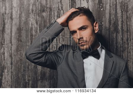 Confident Sexy Man With A Bow-tie Standing On The Grey Background