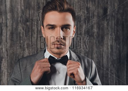 Confident Man Fastening A Bow-tie  On The Grey Background