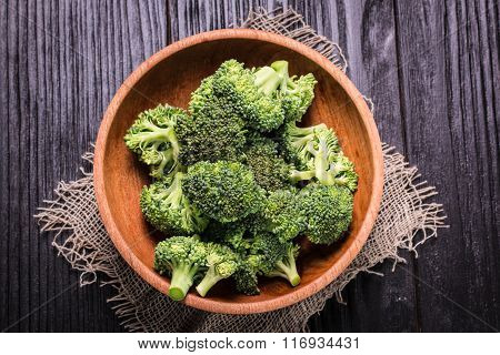 Bunch of fresh green broccoli on brown plate over wooden background