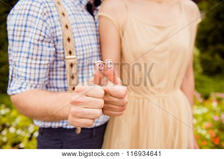 Closeup Photo Of A Happy Couple In Love Holding Wedding Rings On Their Thumbs