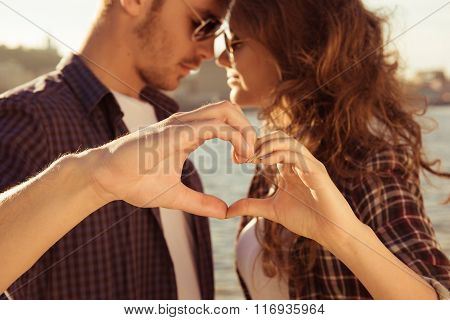 Romantic Tender Couple In Love Gesturing A Heart With Fingers Near River
