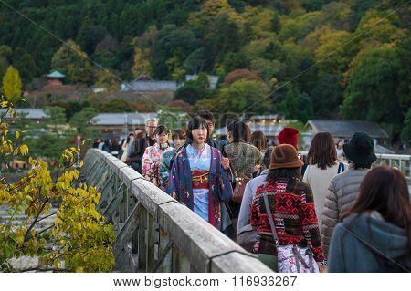 KYOTO JAPAN - NOVEMBER 12 2015: Unidentified Japanese girl with traditional Kimono dress walking on Togetsukyo bridge the famous landmark in Arashiyama with autumn leaves.