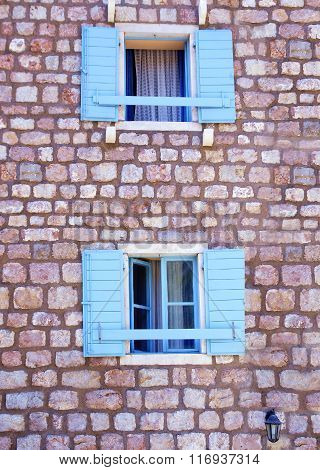 Two Old Wooden Blue Windows On A Stone Wall Of The House