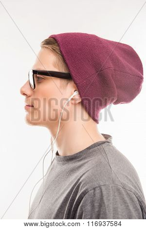Side View Of A Happy Man With Glasses And Hat Litening To Music