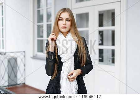 Stylish Young Beautiful Girl In A Black Dress And A White Knitted Scarf On A Light White Background