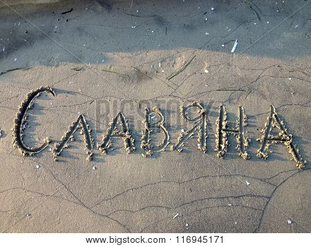 Slavyana female name written in the sand in Cyrillic