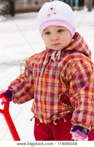Child Playing With Spade In Snow