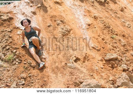 Woman Slides Down Slick Dirt Hill In Obstacle Course Race